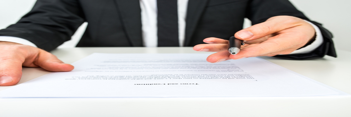 Front view of a businessman offering you to sign a document with focus to the text Terms and Conditions.
